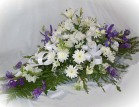 Send an oval shaped sympathy arrangement containing white lilies, roses and other seasonal cut flowers - Click to enlarge